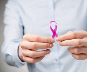 Businesswoman holding a pink breast cancer awareness ribbon close to the camera.
