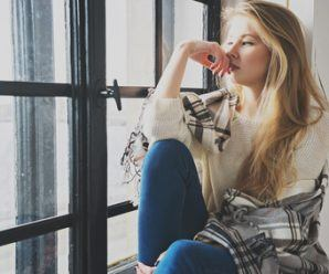 portrait of young blonde woman thinking indoor